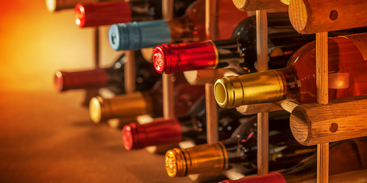 Bottles of wine stacked together in a wine cellar.