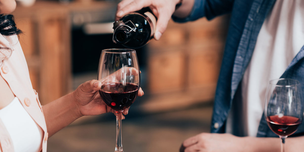 Man pouring red wine for woman in her wine glass