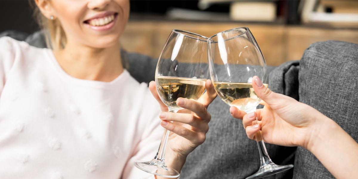 Friends cheering white wine glasses
