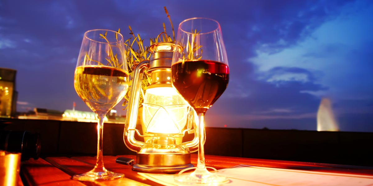 Red and white wine glass on table, with lantern and city skyline in background