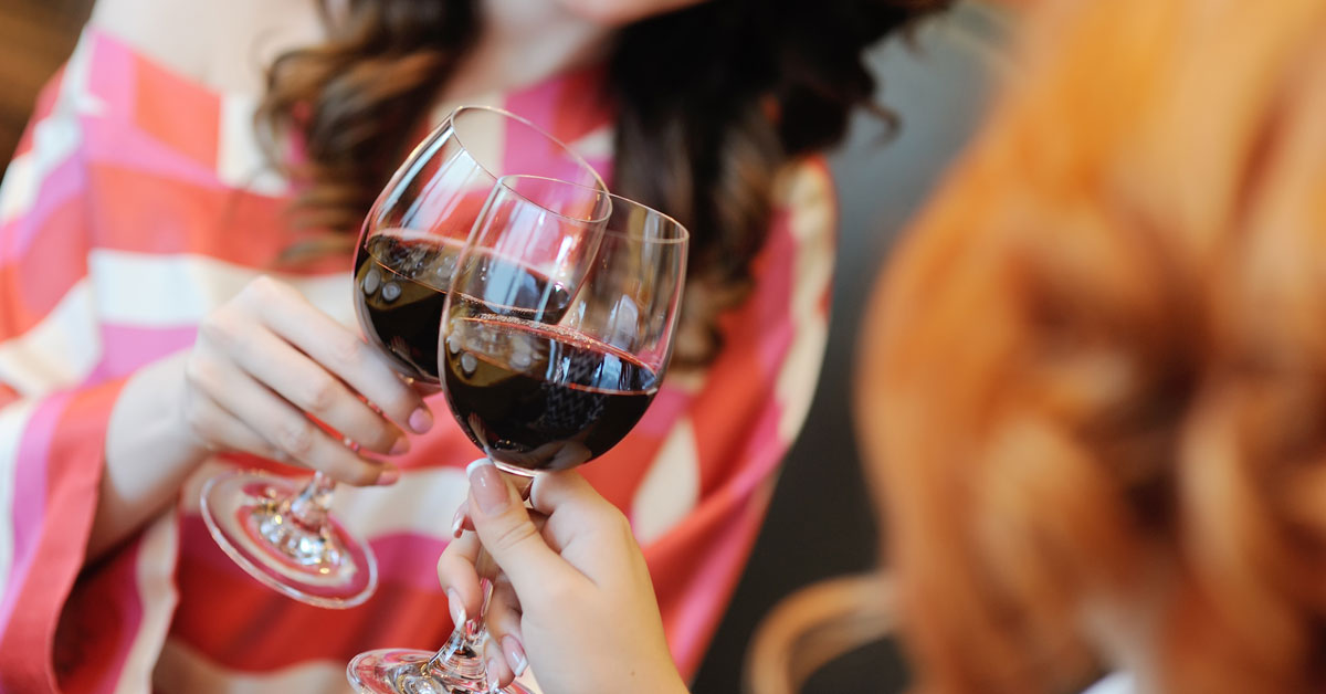 Women toasting with glasses of red wine