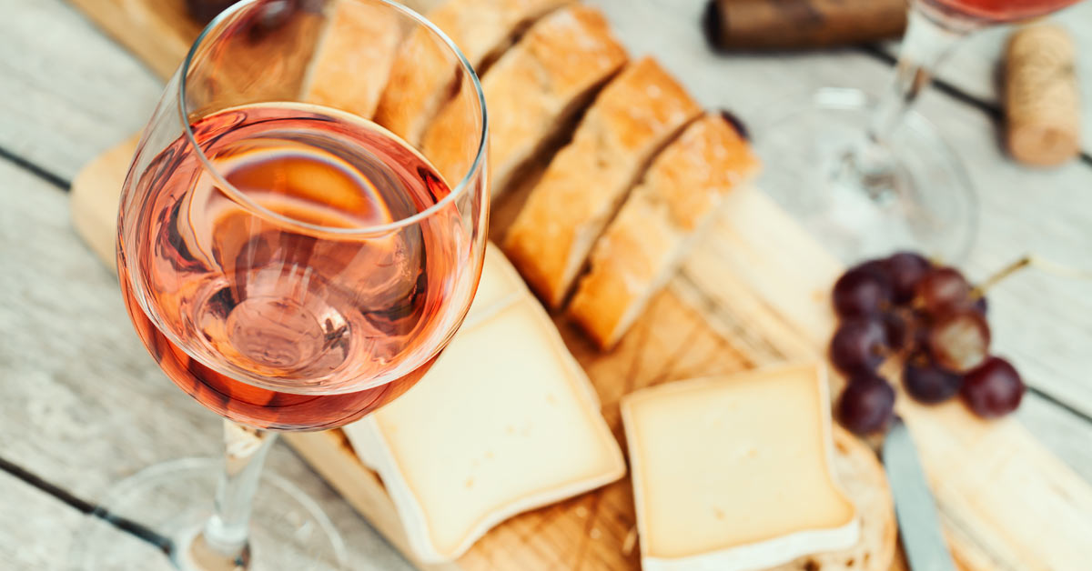 A glass of rose wine, on a picnic table with a cheeseboard