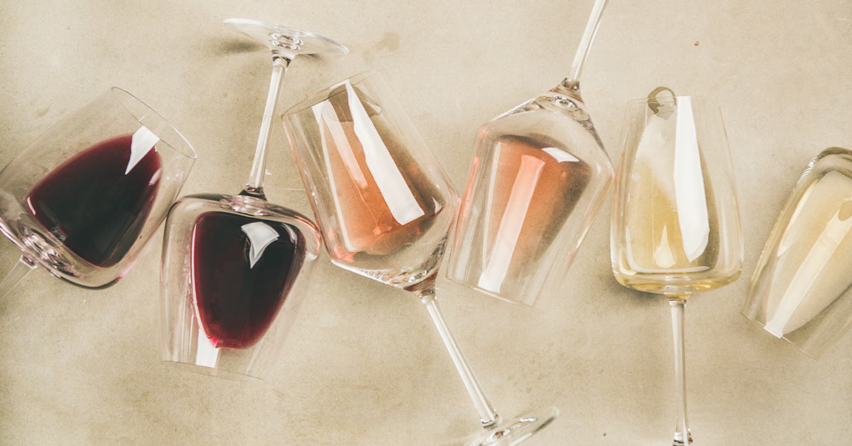 Glasses of red and white wine, laying on a bar top