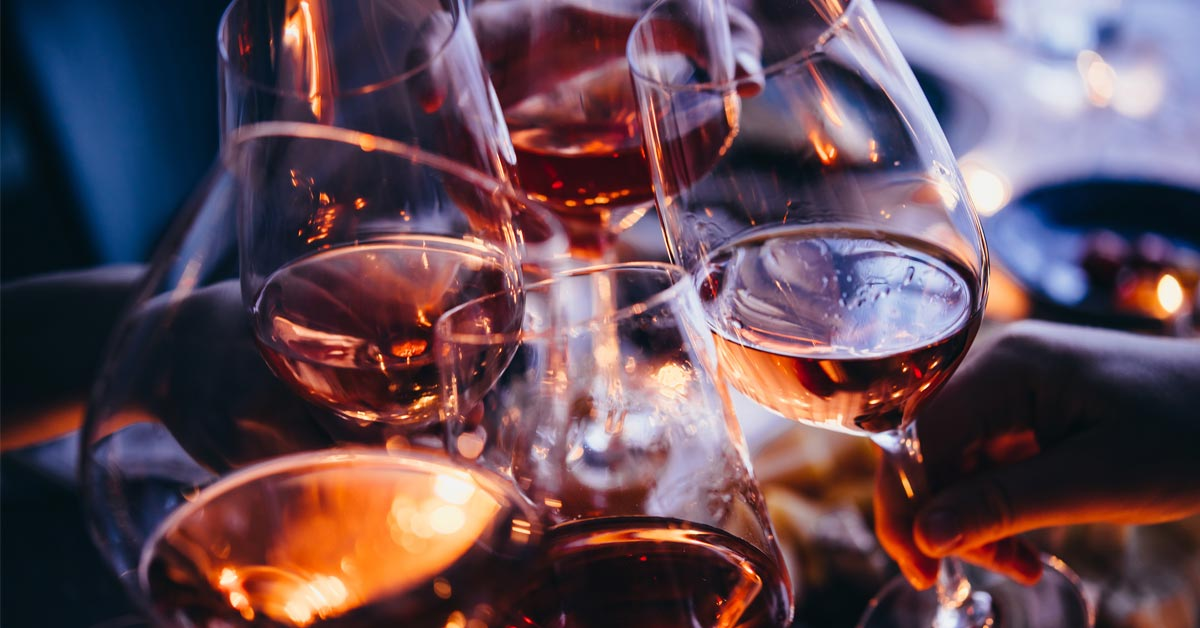 Group of friends toasting together with wine glasses
